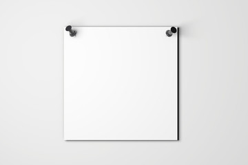 Blank white poster pinned to a plain wall with pushpins