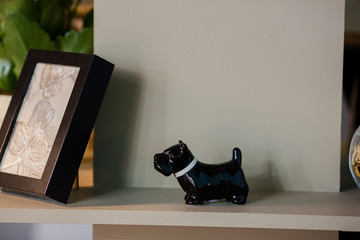 A lonely black porcelain figure of a dog stands on the bookshelf