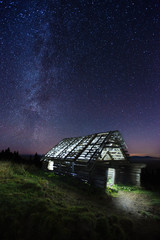 Old abandoned wooden barn under the starry sky
