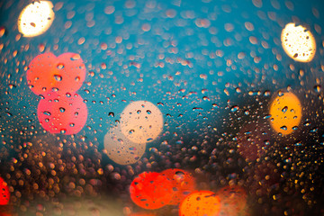 Rain drops on car glass with rain background and bokeh in blue sky before sunset.