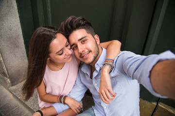 Portrait of beautiful couple in casual wear hugging in the stree