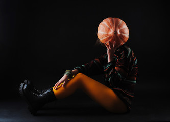 Girl covers her face with a pumpkin