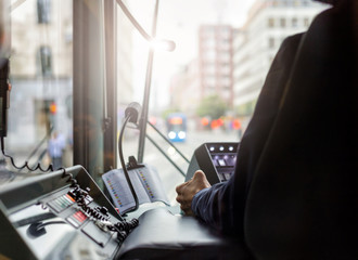 Inside a tram with driver and dashboard in sunset