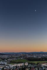 skyline of Linz, Austria with mountains at sun dawn