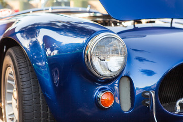 Part of a blue old car with headlamp