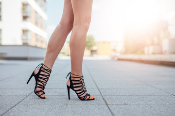 Woman's legs in high heels. Urban background