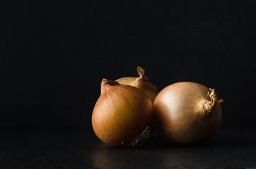 Group of Three Onions on Black  Slate