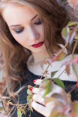 Autumn portrait of a beautiful woman with red hair with bright red lipstick on her lips in the city among the bright colored leaves on a sunny bright day
