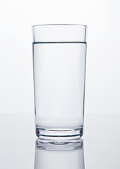 Glass of healthy still drinking water on white