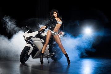 Piękna dziewczyna w seksownym białym stroju z białym motocyklem