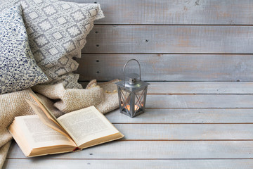 Cushions, plaid, Christmas lantern and old book on the white woo