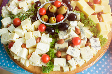 White and yellow cheese, tomato and olives on wooden plate