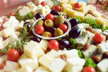 Olives, white and yellow cheese and tomato on wooden plate