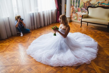 Wedding photographer is shooting portrait of the bride in the studio