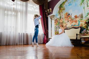 Wedding photographer is shooting portrait of the bride in the studio