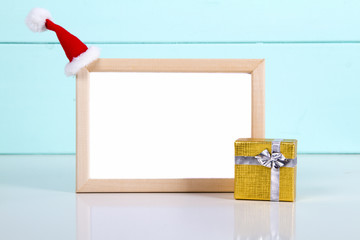picture frame with gift boxes on wooden floor, Santa hats. space for text. mock up