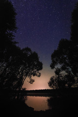 Beautiful night landscape on the forest lake with stars and refl
