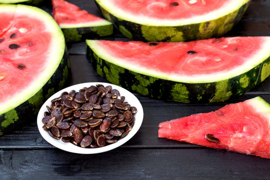 Background of fresh ripe watermelon slices and watermelon seeds on black wooden table. Close up.