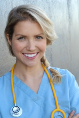 Portrait of happy female nurse with stethoscope standing arms crossed isolated over dark gray background
