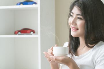 Asian woman relaxing on couch with coffee at home in the living