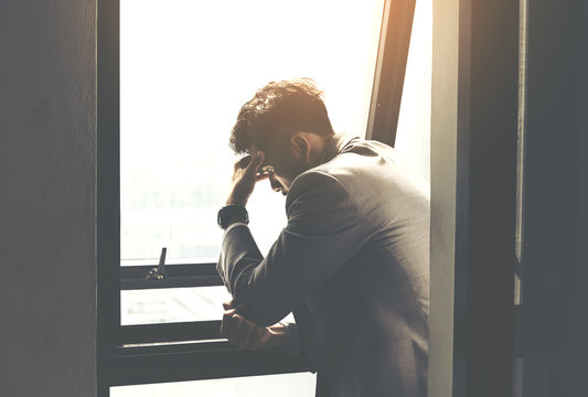 Courageous middle age man looking at the window,Sad and depressed businessman stand alone