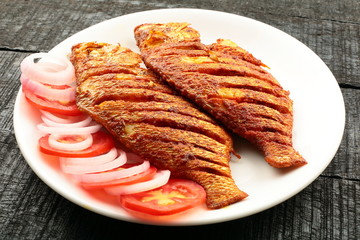 Plate of tasty and spicy fried fish