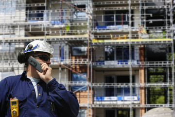 building worker talking in phone against large construction scaffoldings
