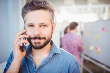 confident businessman listening to cellphone