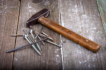 Hammer, nails and screws on a wooden background