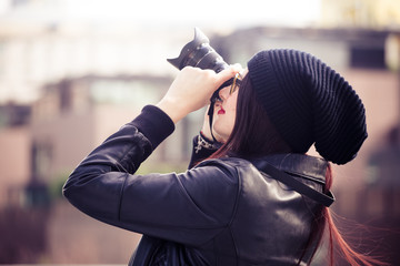 Young beautiful woman taking photo in the city