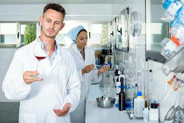 Man checking quality of wine in chemical laboratory