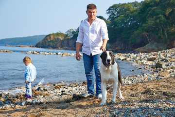 man with his little daughter and a dog walking on the beach
