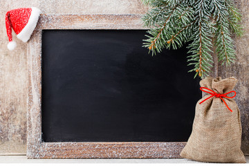 Christmas chalkboard and decoration over wooden background.