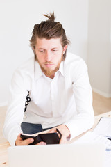 portrait of serious male employee using his private mobile phone to text while working at office