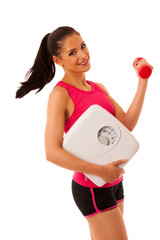 Fit woman holding scale and dumbbell isolated over white backgro