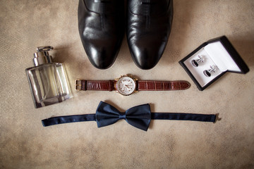 Wedding details. Man accessories. Gromm shoes, hand watch, perfume, bowtie, and box with cufflinks