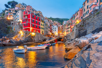 Wall Mural - Riomaggiore fishing village during evening twilight blue hour, seascape in Five lands, Cinque Terre National Park, Liguria, Italy.