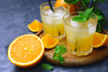 fresh organic orange juice in glass with ice and mint leaf decorated by cut orange fruits on wooden tray.