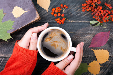 Woman hands holding cup of coffee on autumn wooden background. Old book, autumn leaves and dried rowan on background. Cozy coffee cup. Top view