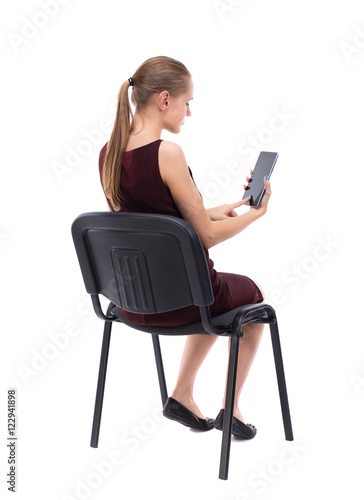 """""""back view of woman sitting on chair and looks at the ..."""