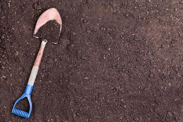 Fototapeta Little shovel partially covered in soil