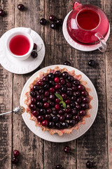 Tart with cherry and whipped cream on wooden vintage table