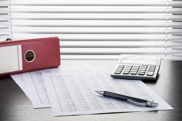 Kugelschreiber, Tabellen, Taschenrechner und Aktenordner auf Schreibtisch vor Fenster mit Jalousie