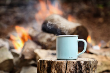 Blue enamel cup of hot steaming coffee sitting on an old log by an outdoor campfire. Extreme shallow depth of field with selective focus on mug. Wall mural