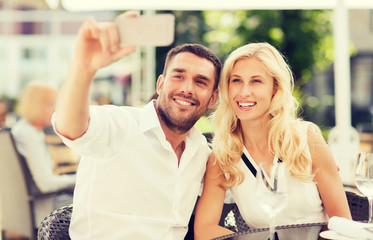 happy couple taking selfie with smatphone at cafe