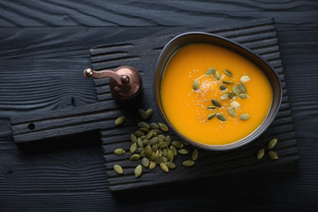 Pumpkin cream-soup over black wooden background, high angle view