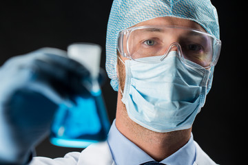 close up of scientist holding flask with chemical