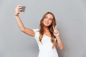 Woman in hat making selfie photo and showing peace gesture
