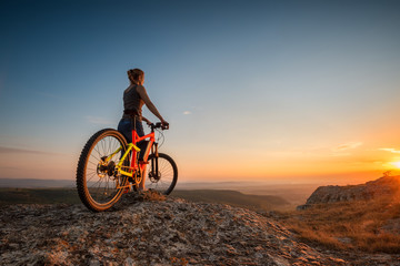 Sunset from the top / A woman with a bike enjoys the view of sunset over an autumn forest