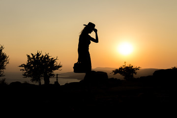 woman silhouette with cowboy hat on hill at sunset